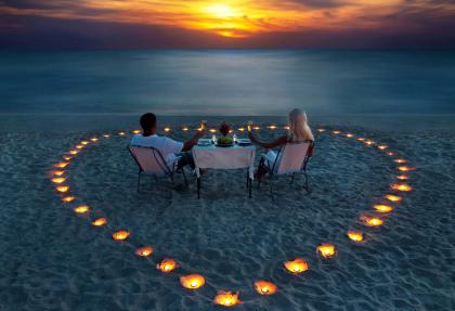 Paar beim Dinner am Strand Hochzeitsreise